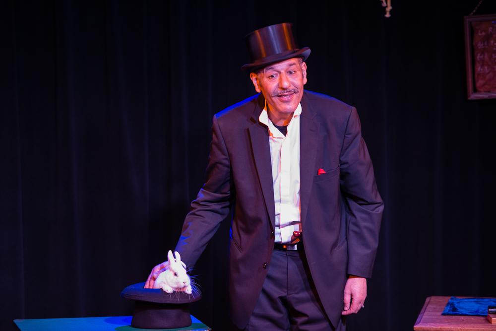 La photo représente Max Zargal le magicien qui caresse un lapin blanc placé dans un chapeau haut de forme.